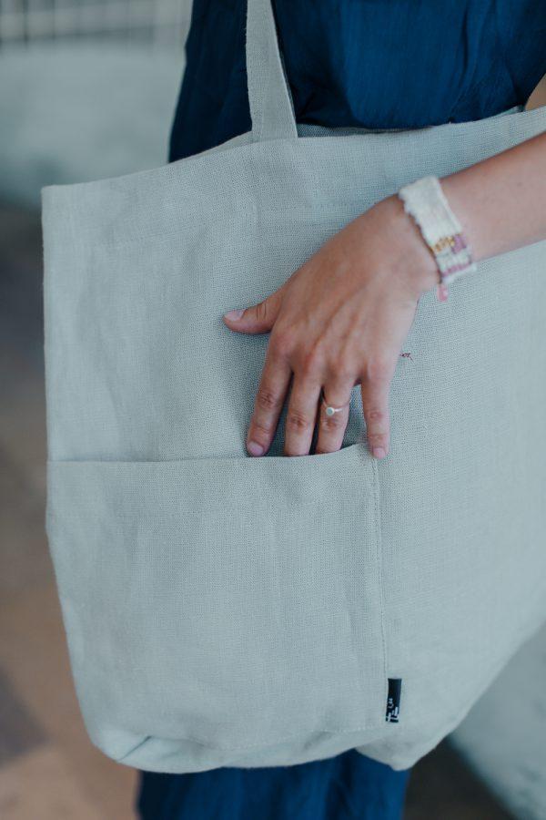 torba lniana MIĘTOWA, ręka włożona w kieszeń zewnętrzną, boczną