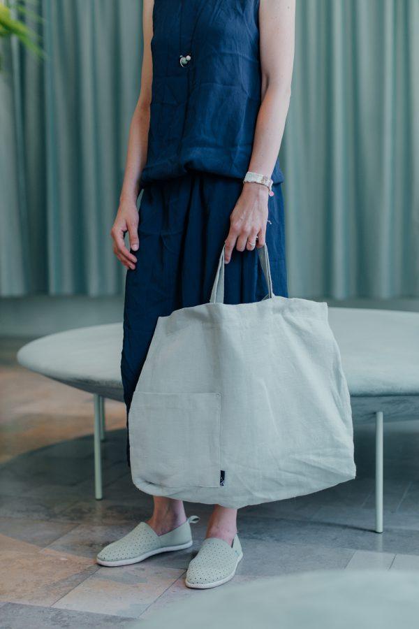 torba lniana MIĘTOWA kobieta trzyma w ręce torbę za krótsze uszy