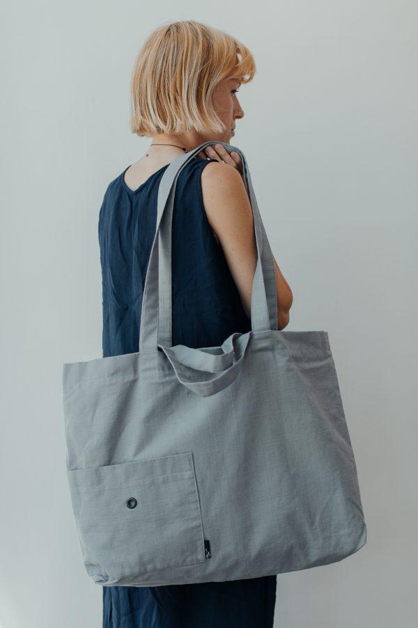 kobieta stoi bokiem na tle białej ściany, z torbą na ramieniu
