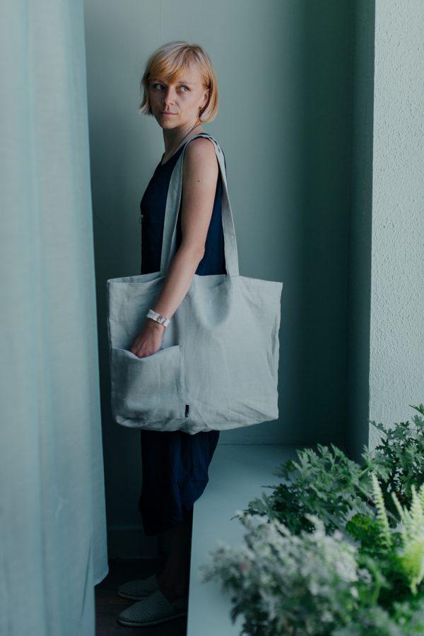 torba lniana MIĘTOWA. kobieta z torbą na ramieniu, z jedną ręką w bocznej kieszeni, stoi bokiem przed miętową ścianą, za poprotką
