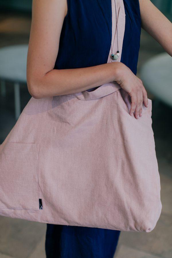 ręka z różową torbą zawieszoną na ramieniu