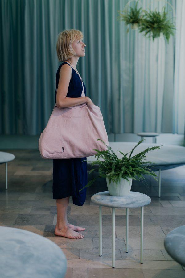 kobieta w granatowej sukience stoi bokiem na tle zasłony w miętowym kolorze, z różową torbą na ramieniu