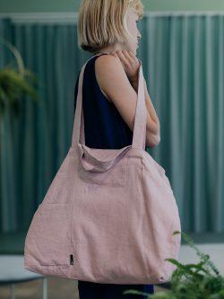 różowa, lniana torba zawieszona na ramieniu dziewczyny stojącej bokiem