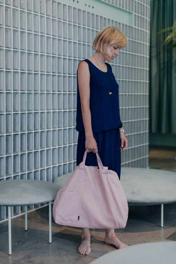 kobieta w niebieskiej sukience stoi z pochyloną głową i trzyma w prawej ręce różową torbę