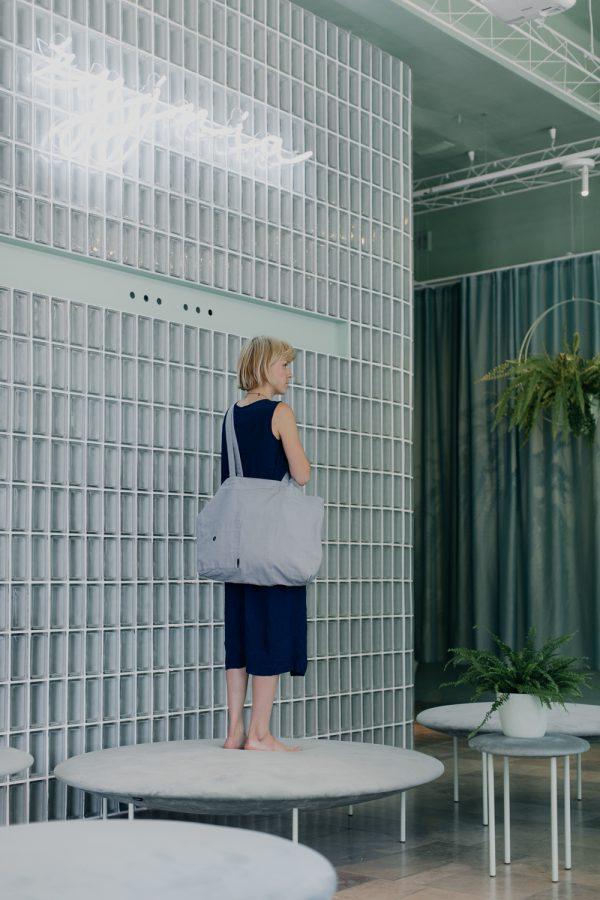 kobieta stoi tyłem z szarą torba lnianą SZARA przewieszoną przez ramię, wśród paprotek, na tle luksferów i zasłony w kolorze miętowym