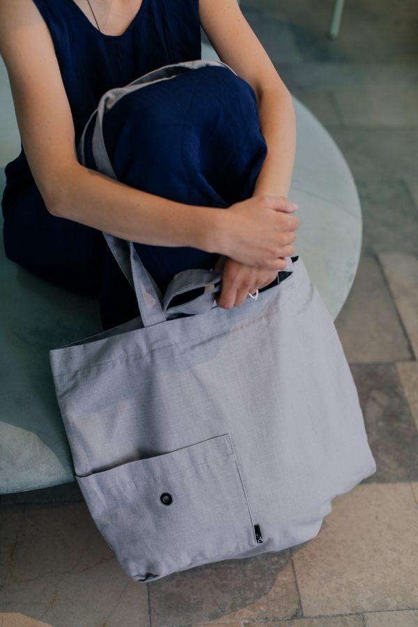 kobieta siedzi na okrągłej miętowej pufie, obejmując rękami kolana, na których zawieszona jest torba lniana SZARA