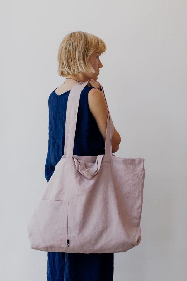 kobieta stoi tyłem na tle białej ściany z różową torbą na ramieniu