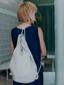 blondynka w granatowej sukience, stoi na tle miętowej zasłony i paproci, z workiem na plecach