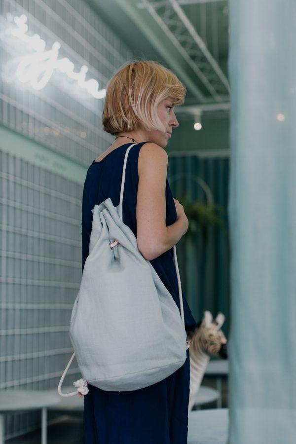 blondynka stoi bokiem, na ramieniu ma zawieszony lniany worek w kolorze miętowym