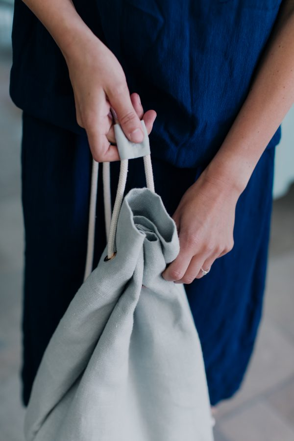 dwie ręce trzymające worek z lnu w kolorze miętowym