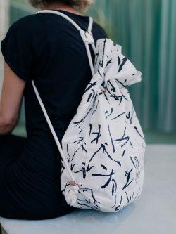 worek lniany MAZAKI. lniany biały worek w czarne kreski na plecach siedzącej dziewczyny