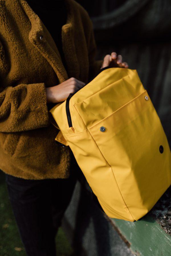 plecak SOLARNA KOSTKA. Damski miejski żółty plecak trzymany w rękach przez dziewczynę.