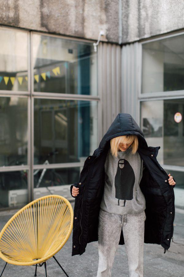 kurtka ŚNIEŻNA CHMURA. Czarna damska kurtka zimowa na dziewczynie obróconej przodem.