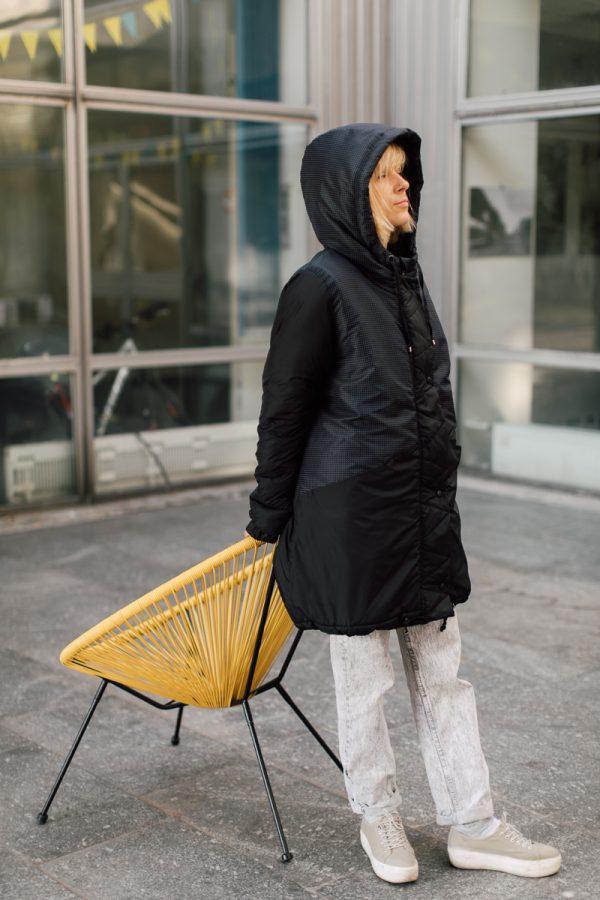 kurtka ŚNIEŻNA CHMURA. Czarna damska kurtka zimowa na dziewczynie obróconej bokiem.