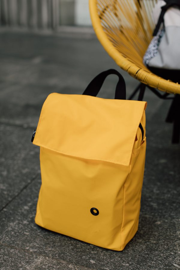 plecak SOLARNA KOSTKA. NIeduży damski miejski plecak koloru żółtego leży na chodniku.