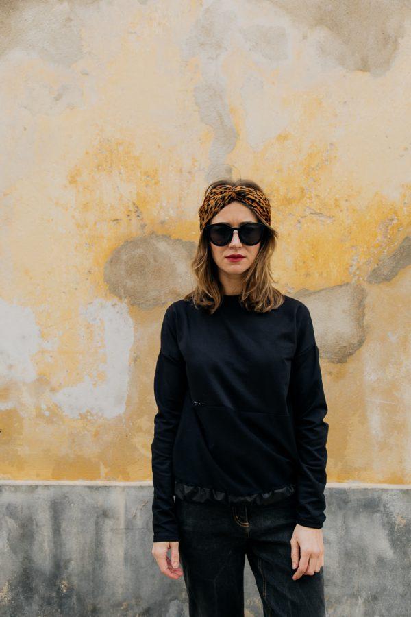 Kobieta w ciemnych okularach, zwrócona przodem, w czarnej bluzie KAWKA, spogląda spogląda w kamerę