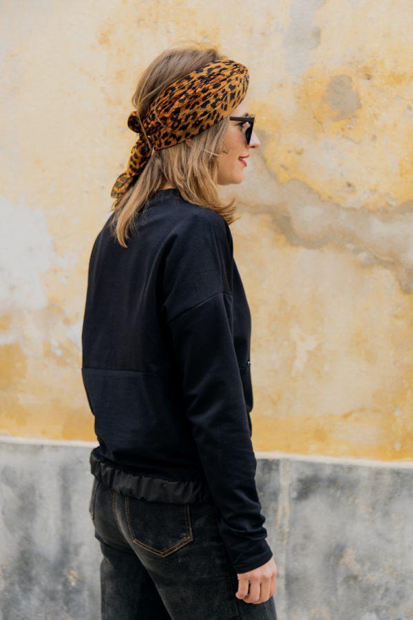 Kobieta w ciemnych okularach, zwrócona bokiem, w czarnej bluzie KAWKA, spogląda spogląda przed siebie
