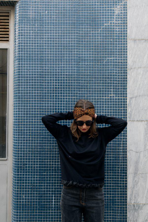 Kobieta w ciemnych okularach, zwrócona przodem, w czarnej bluzie KAWKA, spogląda spogląda w dół.