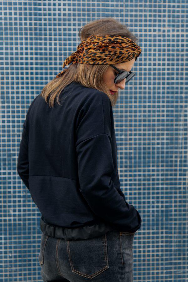 Kobieta obrócona tyłem, w czarnej bluzie KAWKA, spogląda ukosem w dół