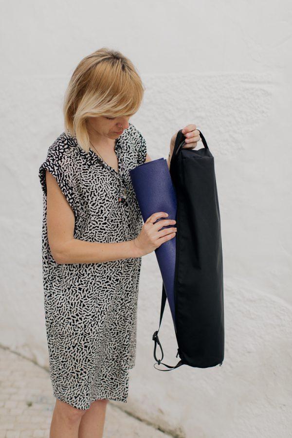 Piękna dziewczyna o blond włosach trzymająca w ręku czarny pokrowiec na matę SUWAK