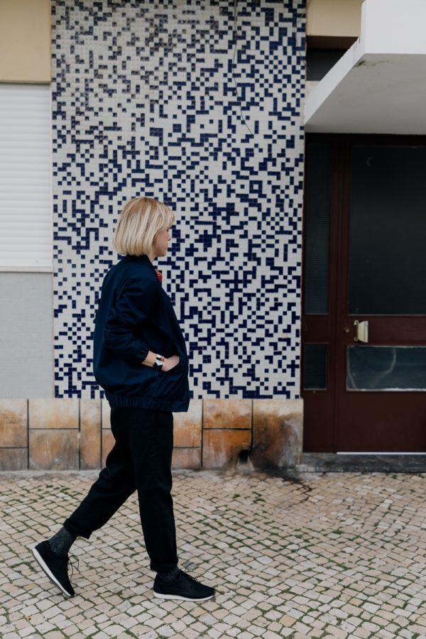 Kobieta, blondynka, w granatowej kurtce bomberce ATRAMENT, idzie chodnikiem.