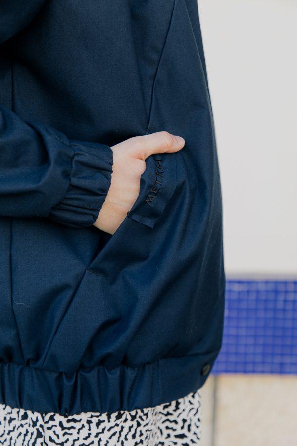 Wycinek kobiety z widoczną ręką włożoną do kieszeni kurtki bomberki ATRAMENT