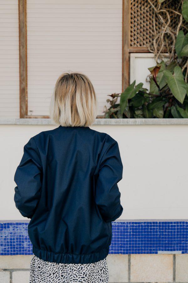 Kobieta, blondynka, w granatowej kurtce bomberce ATRAMENT, obrócona tyłem, spogląda na kwiaty umieszczone na balkonie.