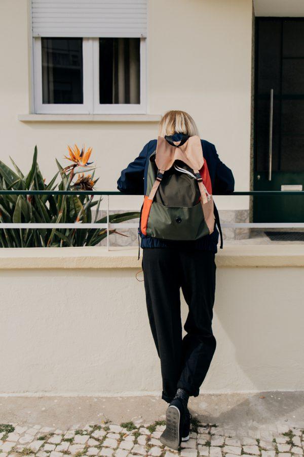 plecak POMARAŃCZE NA SOŚNIE na plecach dziewczyny opartej o barierkę i spoglądającej w dół