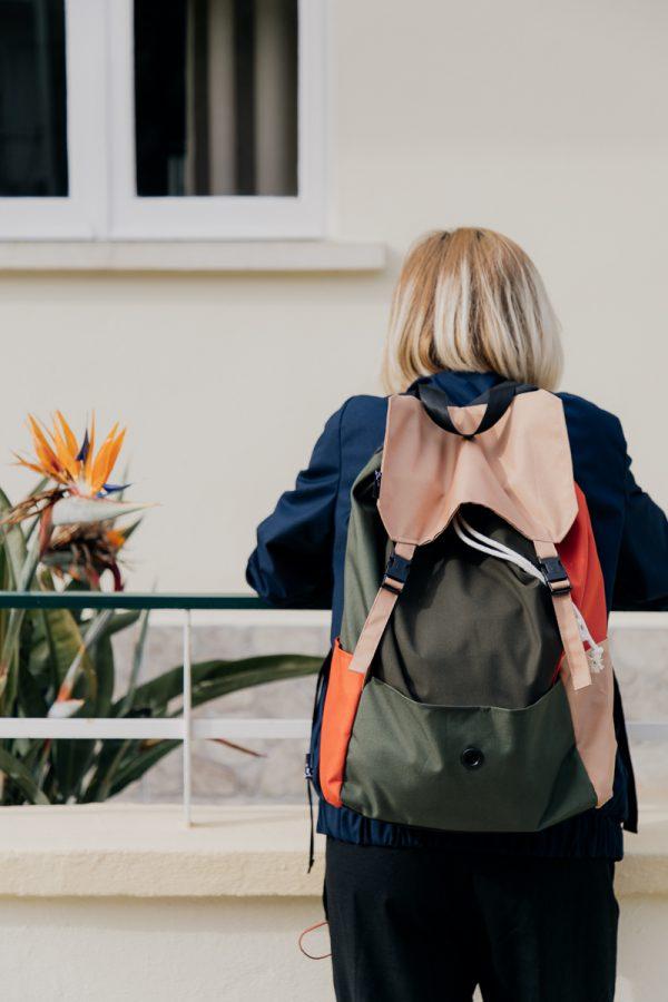 plecak POMARAŃCZE NA SOŚNIE na plecach dziewczyny opierającej się o barierkę