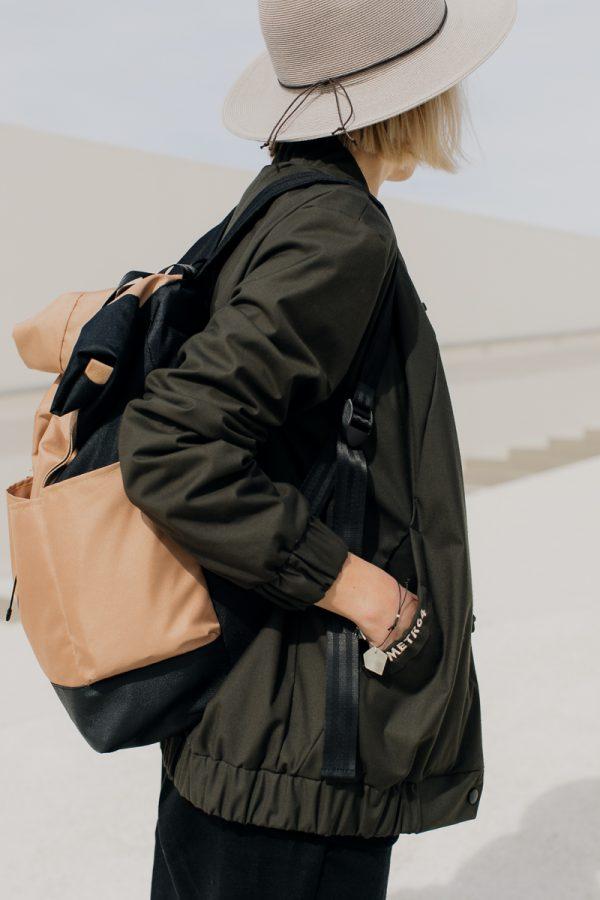 Kobieta, blondynka w kapeluszu obrócona bokiem z ręką w kieszeni, ubrana w damską kurtkę bomberkę SZUWARY