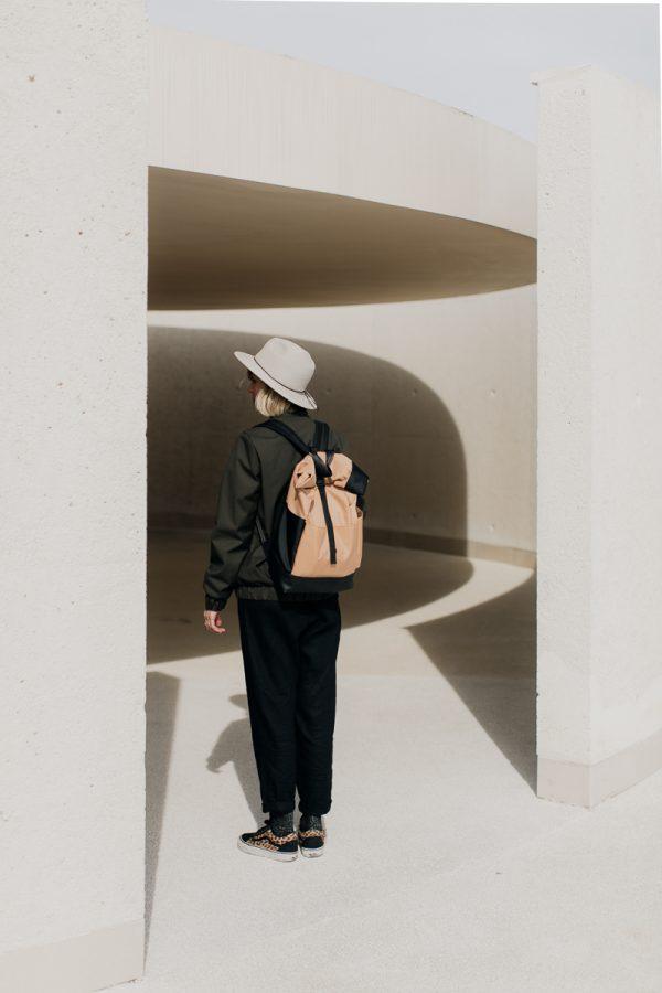 Kobieta, blondynka w kapeluszu obrócona tyłem ubrana w damską kurtkę bomberkę SZUWARY