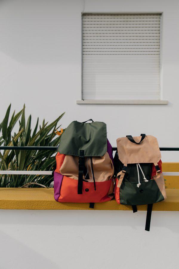 plecak POMARAŃCZE NA SOŚNIE położony obok innego plecaka na murku