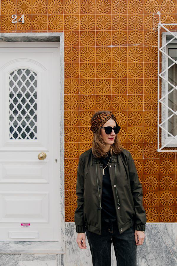 Kobieta w ciemnych okularach spogląda poza kadr, ubrana w damską kurtkę bomberkę SZUWARY