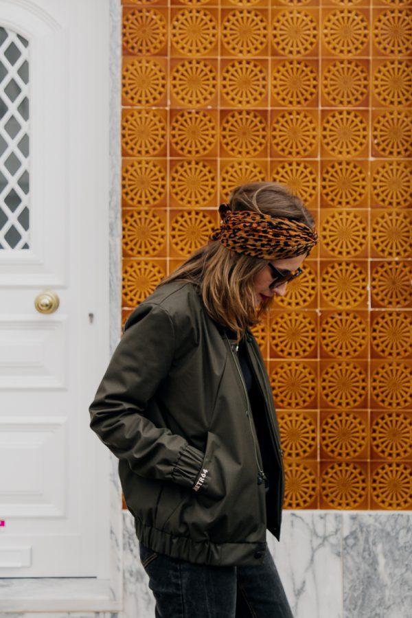 Kobieta w ciemnych okularach spogląda pod siebie, ubrana w damską kurtkę bomberkę SZUWARY