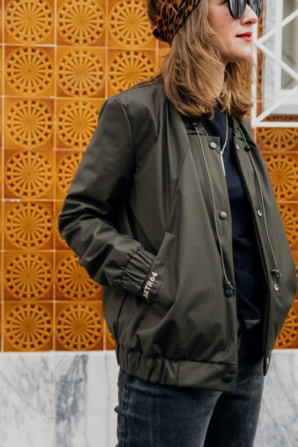 Dziewczyna w ciemnych okularach z rękami w kieszeniach, ubrana w damską kurtkę bomberkę SZUWARY spogląda poza kadr.