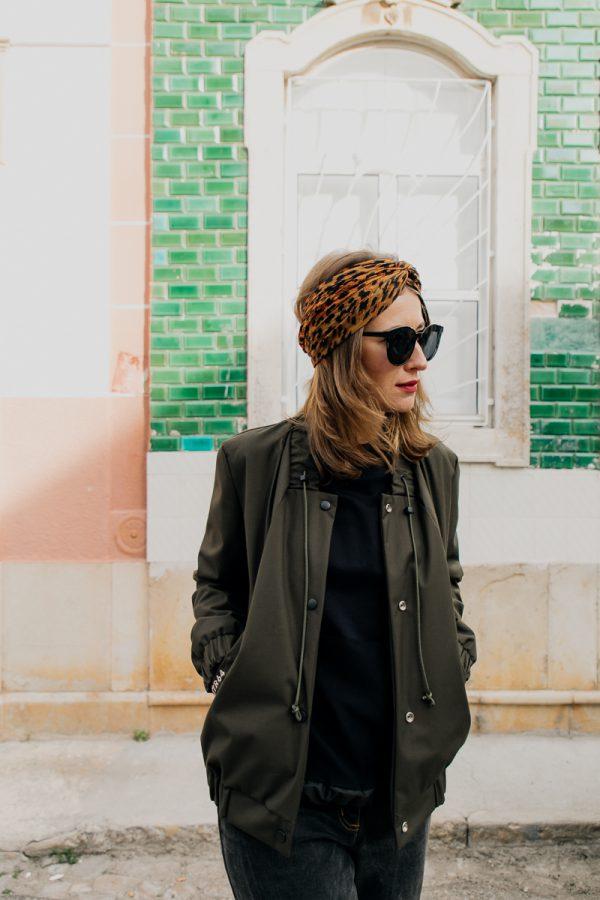 Kobieta w ciemnych okularach idzie w kierunku fotografa, ubrana w damską kurtkę bomberkę SZUWARY