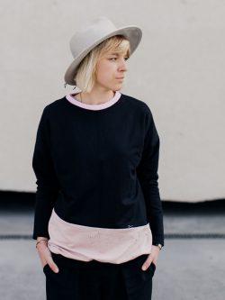 bluza FLAMING. Dziewczyna w czarno różowej bluzie z rękami w kieszeniach.