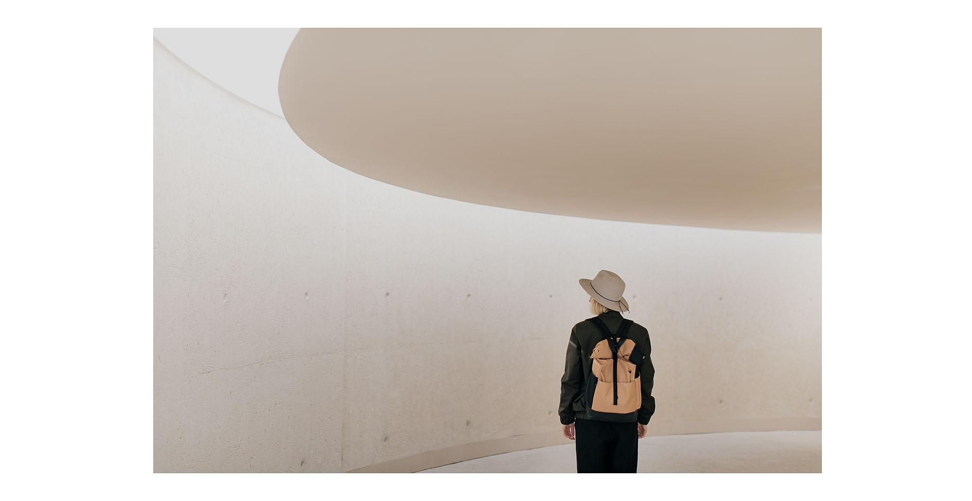 Kolekcja symetria. Kobieta z plecakiem _WIELBŁĄD I KRUK na plecach w kurtce _ Szuwary