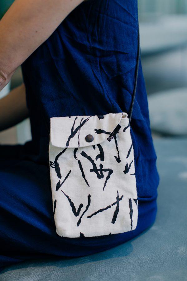 saszetka drobinka MAZAKI. mała torebka na tle niebieskiej sukienki