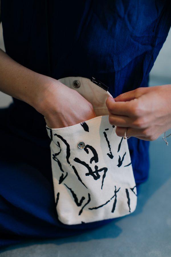 saszetka drobinka MAZAKI ręka damska otwiera podnosi klapkę w małej czarno - białej torebce