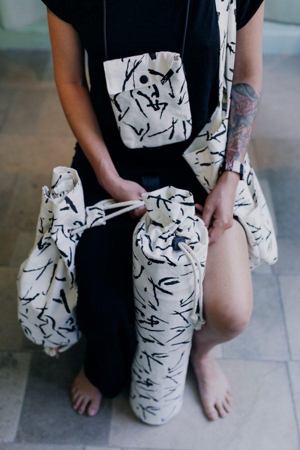 pokrowiec na matę MAZAKI. dziewczyna siedzi przodem z pokrowcem, torbą, saszetką i workiem z czarno - białego lnu