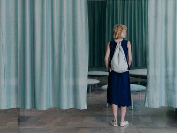 między rozsuniętymi zasłonami w kolorze miętowym, stoi tyłem blondynka z plecakiem na plecach
